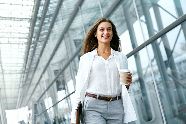 Smiling business woman walking with coffee