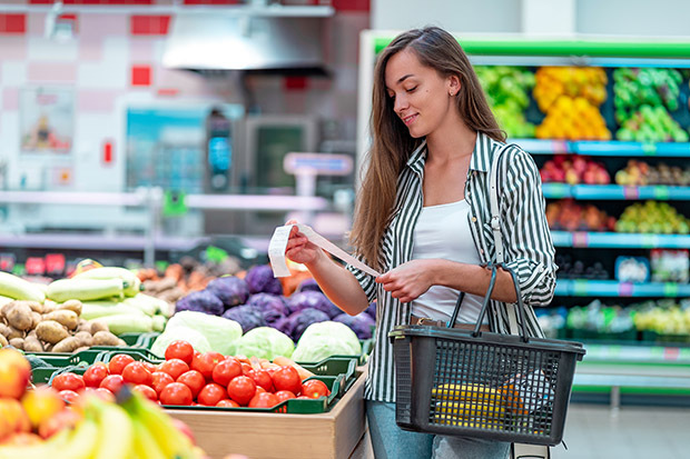 Woman checking shopping list at grocery store