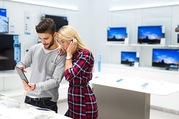Young couple at electronics store looking at ipad