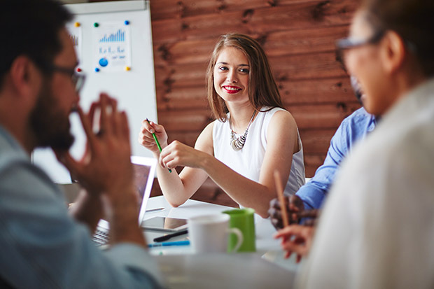 smiling woman at meeting with colleagues
