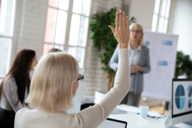 Woman putting hand up in meeting at work