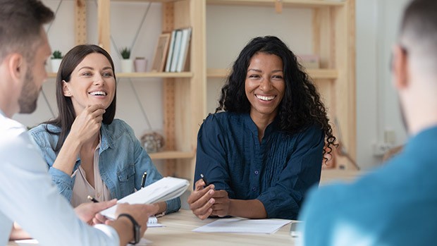 two women in meeting smiling