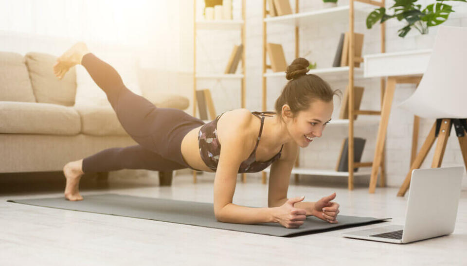 woman doing yoga from laptop