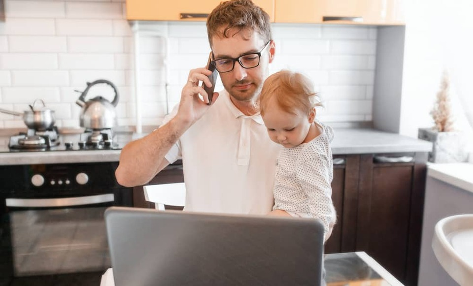 man working at home with baby